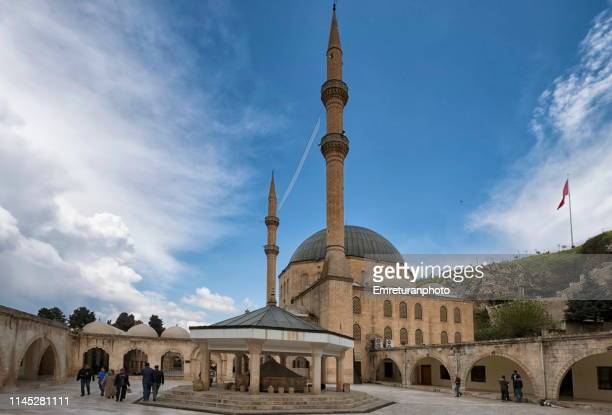general view of dergah mosque courtyard with walking people near sacred fishpond,şanlıurfa. - emreturanphoto stock pictures, royalty-free photos & images