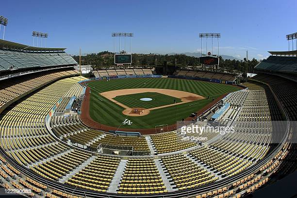 General view of Dodger Stadium as Dodger players warm up in left field and the grounds crew prepares the infield dirt and home plate area before the...