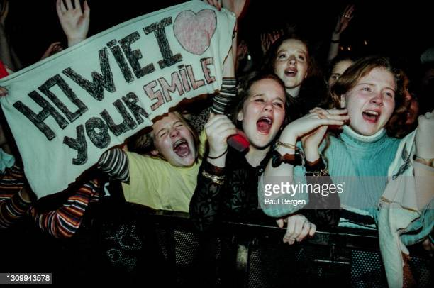 General view of emotional fans in the front rows of the audience, cheering, screaming and holding banners while watching American boyband Backstreet...