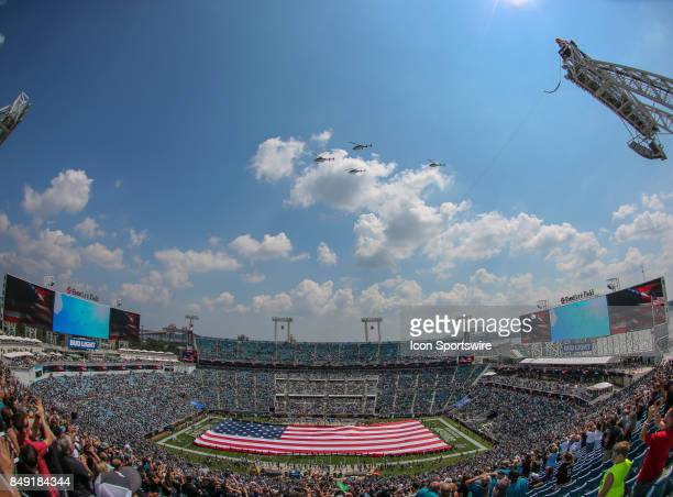 A general view of EverBank Field with a fieldlength American Flag as four Jacksonville Sheriffs Office Police Aviation Unit helicopters flyover prior...