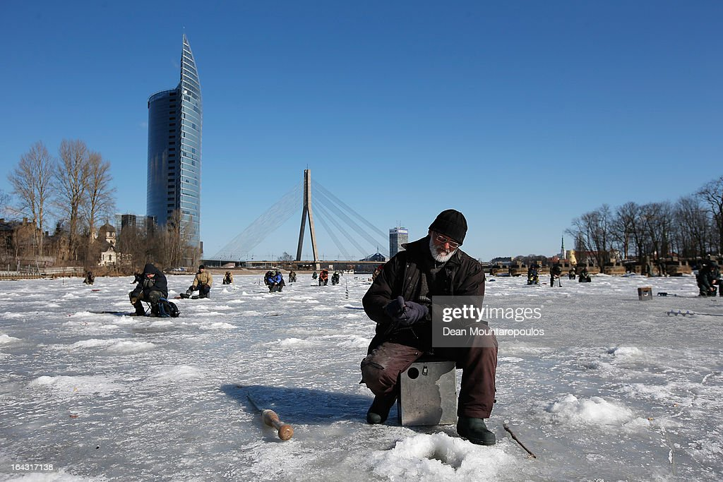 A general view of fishermen on the frozen ice of the Daugava River with the Shroud Bridge or Vansu tilts in the background on March 22, 2013 in Riga, Latvia.