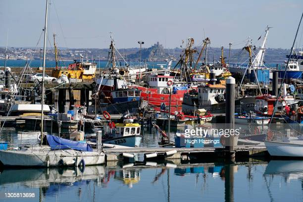 """General view of fishing boats in port with St Michael""""u2019s Mount in the distance on March 7, 2021 in Newlyn, England. While Prime Minister Boris..."""