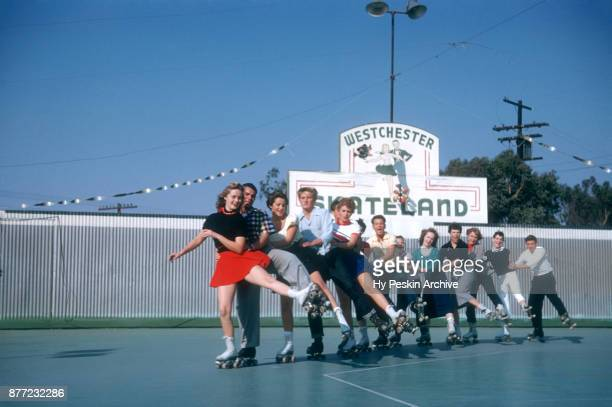 General view of Gloria and her friends roller skating in a conga line circa November 1954 at the Westchester SkateLand in Westchester New York
