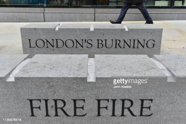 A general view of granite stone benches showing the words London's Burning and Fire Fire of the London's Burning rhyme engraved onto the surface...