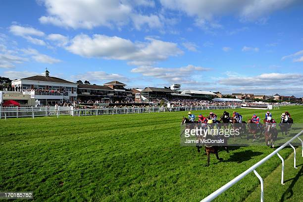 General view of horses and jockeys as they pass the grand stand during racing at Stratford-upon-Avon racecourse on June 8, 2013 in...