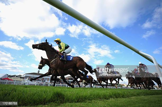 A general view of horses and jockeys as they pass the grand stand during racing at StratforduponAvon racecourse on June 8 2013 in StratforduponAvon...