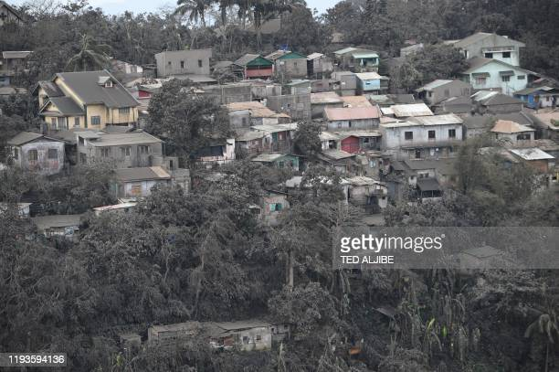 TOPSHOT A general view of houses with roofs covered with ash spewed by Taal volcano in Tagaytay city south of Manila on January 14 2020 Taal volcano...