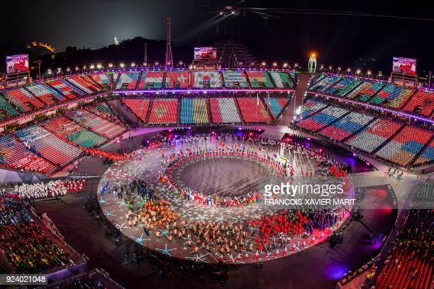 TOPSHOT General view of images of flags being projected on the stands as athletes enter the stadium during the closing ceremony of the Pyeongchang...