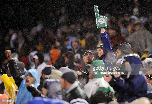 A general view of Jets fans sitting in the rain holding up a foam finger during a game between the New York Jets against the Denver Broncos on...