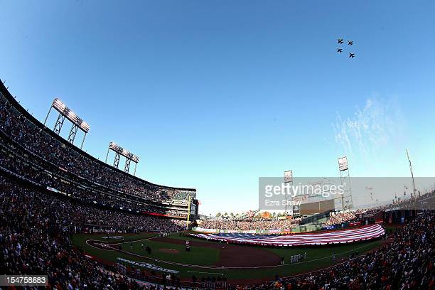 General view of Jets performing a flyover as a giant American Flag is stretched across the outfield for the performance of the National Anthem prior...