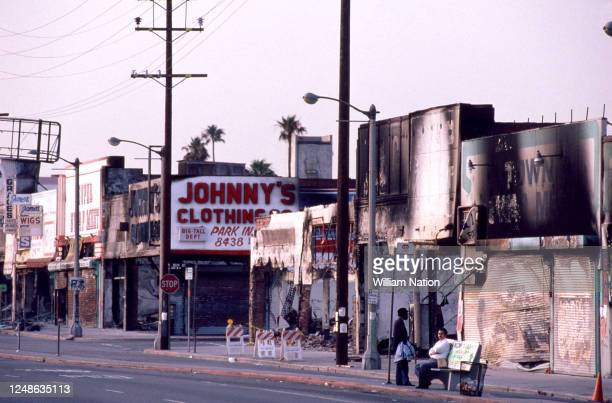 General view of Johnny's Clothing and other stores at the corner of 85th Street and Figeuroa Street showing the charred remains after being set on...