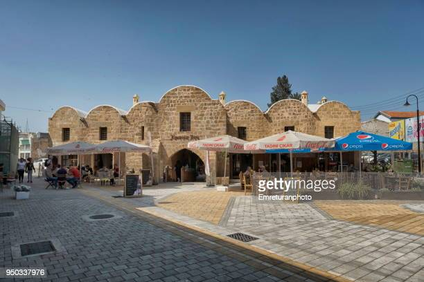 """general view of """"kumarcilar han"""" with tourists sitting and dining under sunshadesin nicosia. - emreturanphoto stock pictures, royalty-free photos & images"""