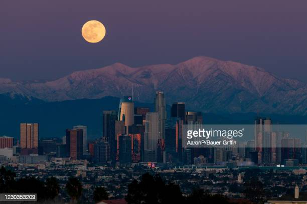 General view of moonrise over Downtown Los Angeles against the snowy San Gabriel Mountains on December 29, 2020 in Los Angeles, California.