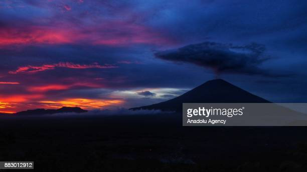A general view of Mount Agung is seen as it spewing smoke and ash during sunset from Lempuyang village of Karangasem Regency in Bali Indonesia on...