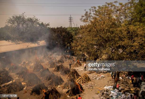 General view of multiple burning funeral pyres of patients who died of the Covid-19 coronavirus disease at a crematorium on April 24, 2021 in New...