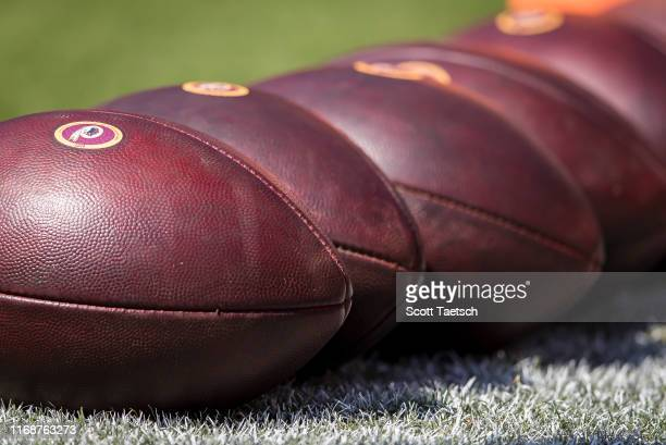 General view of official National Football League balls with Washington Redskins logos on the field before the game between the Washington Redskins...