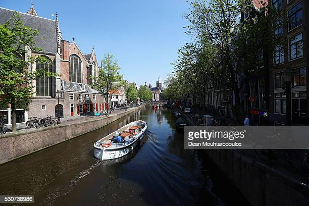A general view of Oude Kerk Oudekerksplein a canal and boat from on the Oudekerksbrug bridge and Oudekennissteeg on May 11 2016 in Amsterdam...