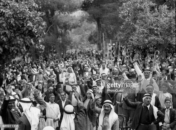 General view of Palestinian Arabs as they raise their arms in agreement during an outdoor rally Abou Ghosh thenMandatory Palestine early to mid1936...