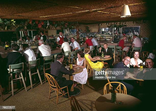 General view of patrons as they drink, smoke, and talk under the thatched roof of the bar & lounge at the Stowaway Motel, Ocean City, Maryland, 1960s.
