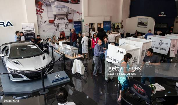 General view of people queue to vote during the presidential election at a polling station on a luxury car dealer in Polanco Mexico City on July 1...