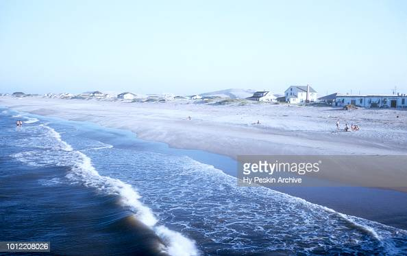 General view of people sun tanning on the beach along the ...