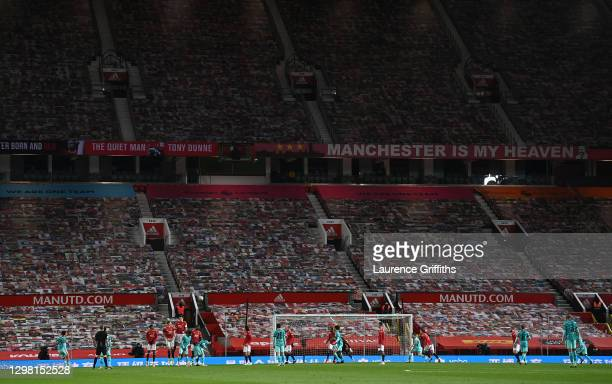 General view of play as Trent Alexander-Arnold of Liverpool takes a free kick in front of the empty stand that is covered in pictures of fans during...