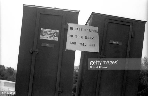 General view of portable toilets are shown with a sign that reads 'In Case of A Fire Go To A Dorm And Dial 333' during The Alternative Media...