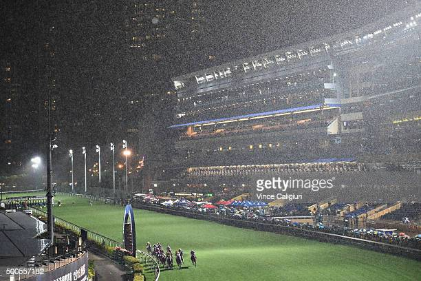 General view of Race 5 as the field races past the post the first time in the pouring rain during Longines International Jockey's Championship night...