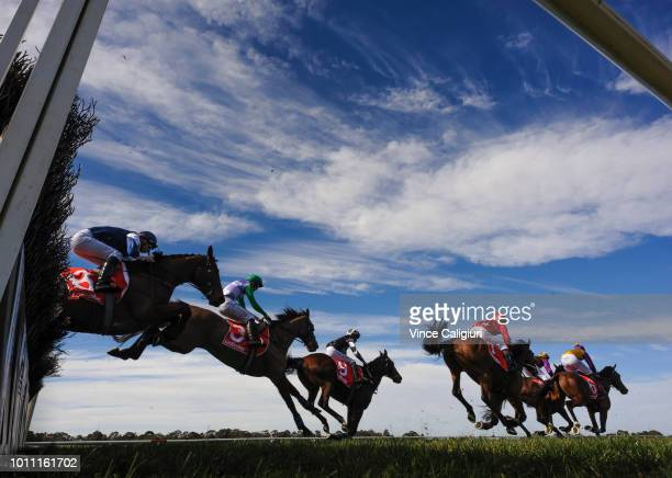 General view of riders and horses jumping the last in Race 1 Crisp Steeplechase during The Grand National Hurdle day at Sandown on August 5 2018 in...