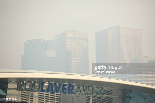 General view of Rod Laver Arena with the city shrouded in smoke in the background ahead of the 2020 Australian Open at Melbourne Park on January 14,...