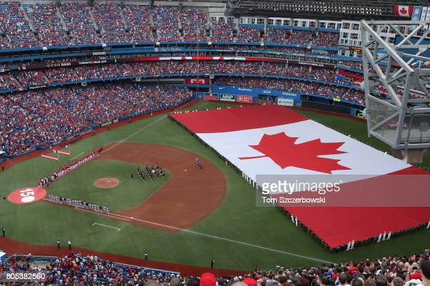 A general view of Rogers Centre as a large Canadian flag is unfurled in the outfield on Canada Day during the playing of the Canadian national anthem...