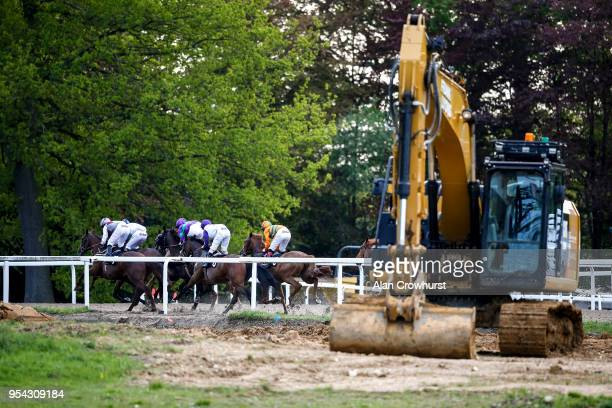 A general view of runners as they pass a digger on the infield preparing the grass inner track at Chelmsford City racecourse on May 3 2018 in...