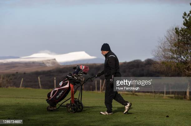 General view of Snow Capped Pen-Y-Fan Mountain in the Brecon Beacons as a man walks across the fairway of a golf course on December 6, 2020 at...