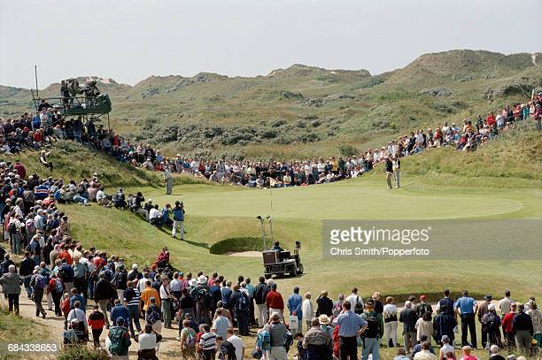General view of spectators watching a professional golfer about to take a putt on a green on the course during competition in the 1998 Open...