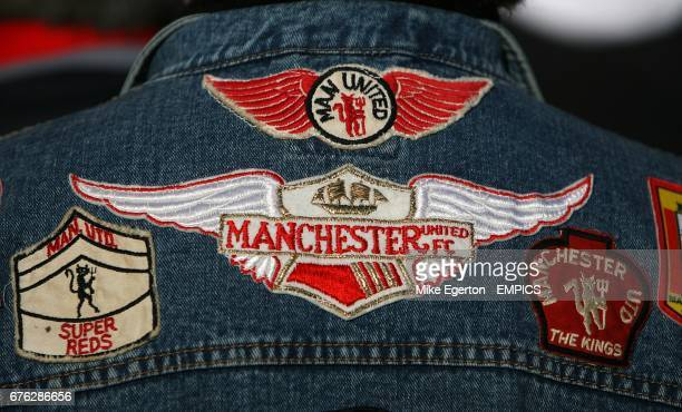 General view of the back of a Manchester United fan's Denim jacket with logos and badges on of Manchester United