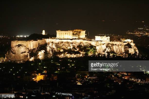 General view of the city of Athens is seen aqt night with dropback of a lit up temple of Parthenon atop the ancient Acropolis on August 8, 2004 in...