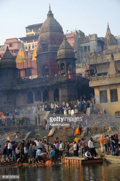 A general view of the cremation ground in Manikarnika Ghat seen from the Ganga River with peopleu2019s activity burning pyres cows hanging around and...