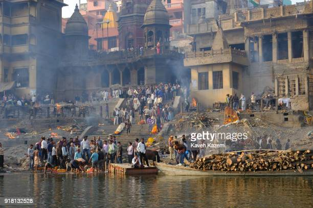 A general view of the cremation ground in Manikarnika Ghat seen from the Ganga River with people'u2019s activity burning pyres cows hanging around...