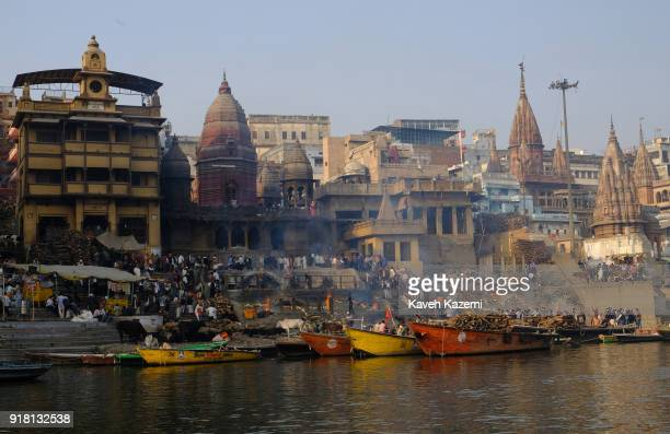"General view of the cremation ground in Manikarnika Ghat seen from the Ganga River with people""u2019s activity, burning pyres, cows hanging around..."