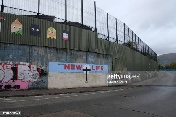A general view of the Cupar Way with a mural showing a cross and written words promising a u201cNEW LIFEu201d painted under the high wall and fences...