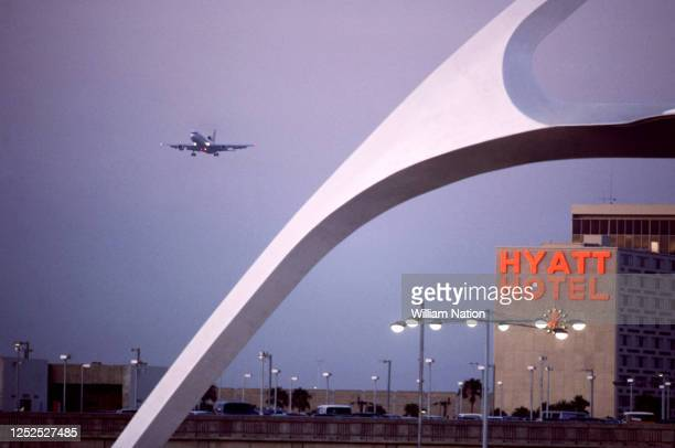 General view of the distinctive white Googie Theme Building is seen as a plane comes in for the landing circa July, 1984 at the Los Angeles...