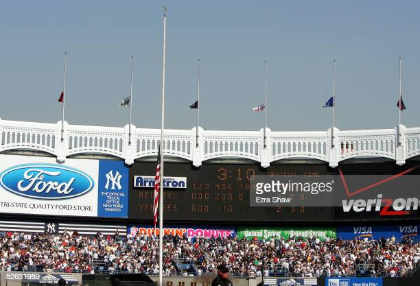 General view of the facade atop the scoreboard which stretchs across the rear of the bleachers as flags fly at halfmast as a symbol of mourning for...