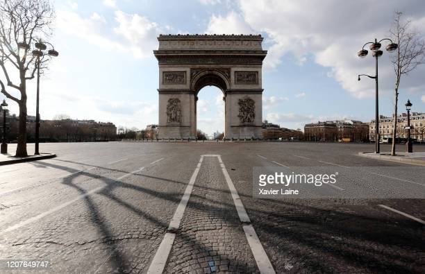 """General view of the French Arc de Triomphe empty, at the end of the empty street """"Avenue des Champs Elysees, while the city imposes emergency..."""