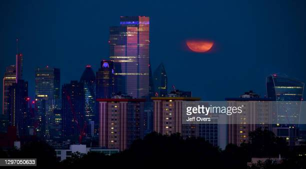 General view of the last Super Moon of the year peeping through the haze above the City of London, England, on the 7th May 2020.