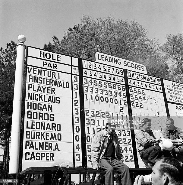 A general view of the main leaderboard with workers reclining during the 1960 Masters Tournament at Augusta National Golf Club in April 1960 in...