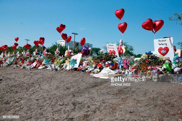A general view of the makeshift memorial in front of Marjory Stoneman Douglas High School as staff teachers and students walk out of classes to...