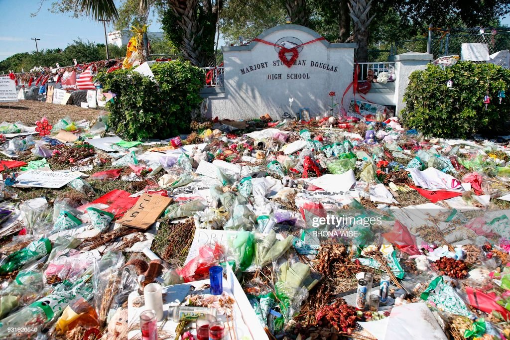 A general view of the makeshift memorial in front of Marjory Stoneman Douglas High School as staff, teachers and students walk out of classes to protest gun violence in Parkland, Florida on March 14, 2018. Students across the US walked out of classes on March 14, in a nationwide call for action against gun violence following the shooting deaths last month at a Florida high school. The nationwide protest is being held one month to the day after Nikolas Cruz, a troubled 19-year-old former student at Stoneman Douglas, unleashed a hail of gunfire on his former classmates. WISE
