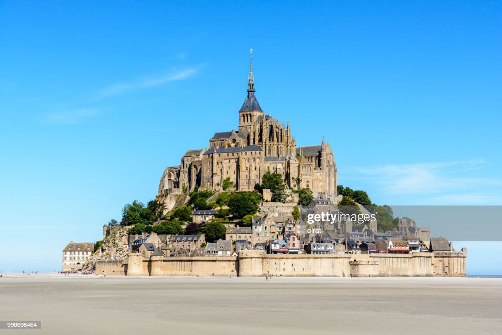 General view of the Mont Saint-Michel tidal island, located in France on the limit between Normandy and Brittany, with the exposed sand of the bay at low tide in the foreground under a blue sky. : Stock Photo