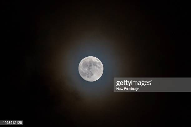 General view of the moon showing a illuminated ring reflection through the clouds on December 28, 2020 at Blackwood, Wales, United Kingdom.