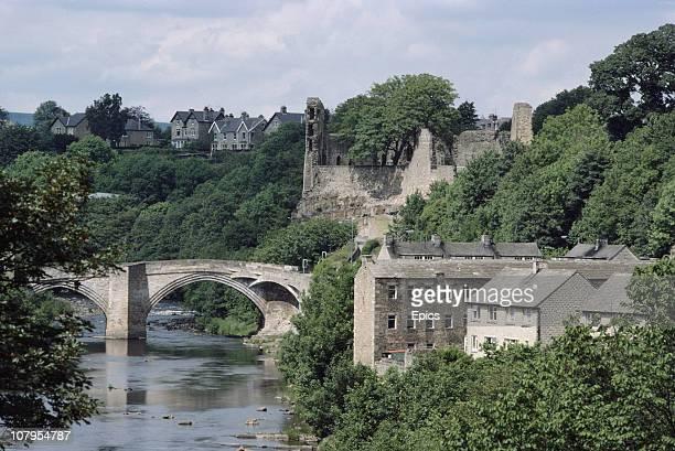 A general view of the partial ruins of Barnard Castle and the country bridge which crosses the river Tees Castle Bernard Teesdale County Durham June...